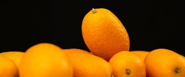 バナーキンカン、黒い背景に新鮮な柑橘系の果物。ヒメタチバナ、健康食品、ローフードのコンセプト。スペース写真をコピーする