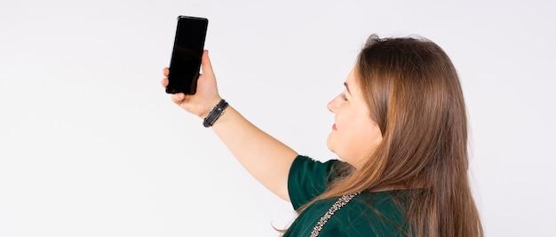 긴 배너 형식의 여성이 휴대전화를 손에 들고 있는 녹색 드레스를 입고 셀카를 아름다운 여성으로 만들고 있습니다.