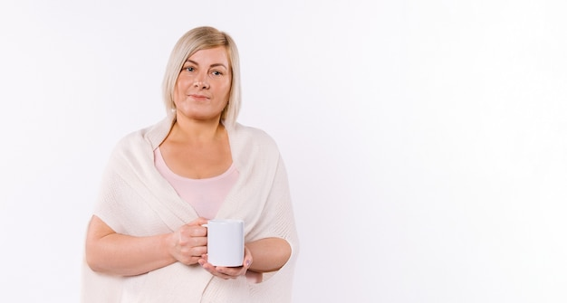 バナー、ロングフォーマット。年配の女性は、空のサイドスペースのある白い皿の上に香りのよいお茶を飲みながら休んでいます。高品質の写真