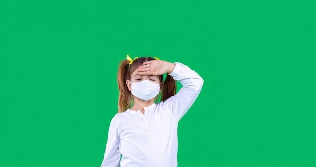 긴 형식의 녹색 배경에 한 소녀가 서 있는 배너는 보호 마스크를 쓰고 이마에 왼손을 들고 있습니다.