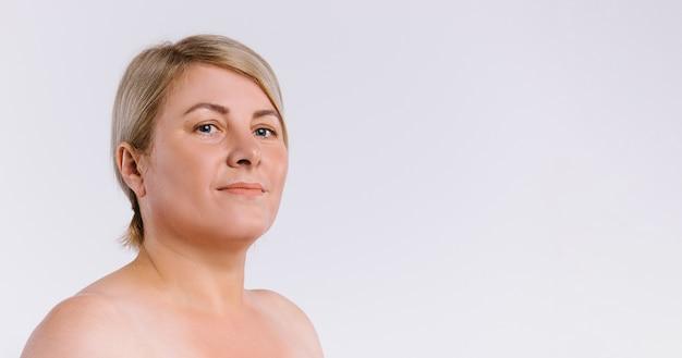 バナー、ロングフォーマット。白地に清潔で色白の肌を持つ年配の女性。自然の美しさ
