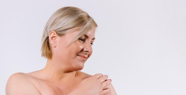 バナー、ロングフォーマット。デリケートなお肌の笑顔の年配の女性が目をそらし、体を楽しんでいます。側
