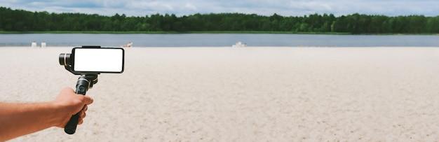 배너, 한 남자의 손에 있는 스테디캠에 있는 스마트폰 모형. 모래 해변과 호수가 있는 자연을 배경으로.