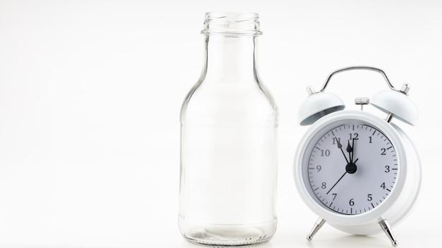 화려한 배경 복사 공간에 흰색 알람 시계가 있는 우유 한 잔의 배너