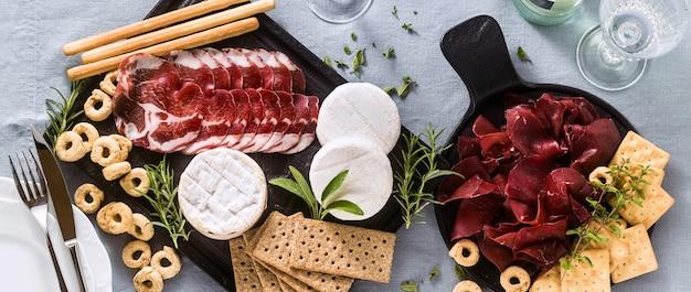 Баннер из мясного ассорти и сыра подается на подносе на столе с белым вином, крекерами, гриссини и таралли с ароматными травами на синей льняной праздничной скатерти.