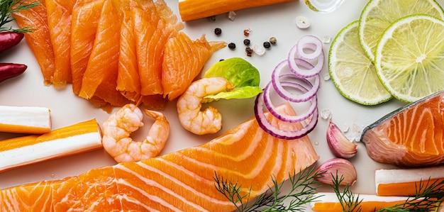 スパイス、野菜、オリーブオイルのテーブルに新鮮な魚介類のバナー:スーパーや魚の寿司レストランの新鮮なスモークサーモン、エビ、カニの棒。