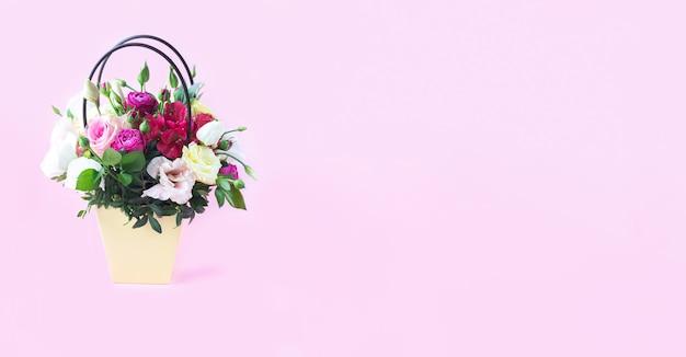淡いピンクの背景に美しい花の花束(バラ、トルコギキョウ、フリージア)とギフトボックスのバナー