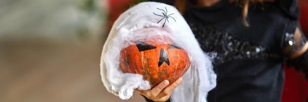 カボチャジャックまたはローランとハロウィーンの衣装で自宅でマスクの女の子のバナー