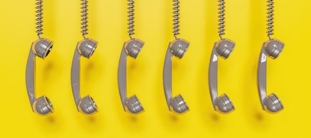 黄色の背景にケーブルからぶら下がっている灰色のアンティーク電話ヘッドセットのバナー。 3dレンダリング