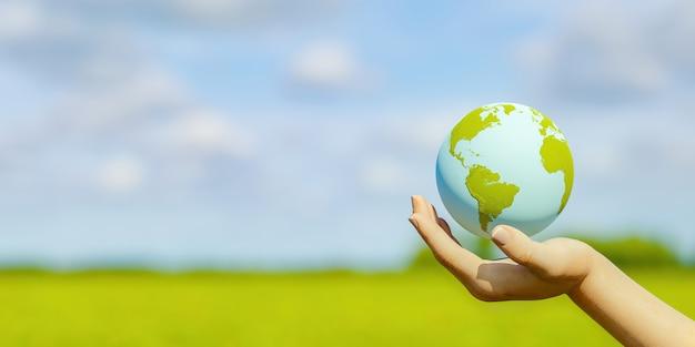背景にぼやけたフィールドと惑星地球を持っている手のバナー。気候変動の概念。 3dレンダリング