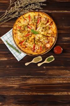 Баннер домашней пиццы из морепродуктов с креветками, крабовыми палочками, перцем на деревянном подносе, стол, украшенный томатным соусом, кетчупом, ингредиентами орегано с салфеткой на кухне и копией пространства.