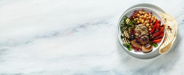 ババガヌーシュカラメル玉ねぎ、スパイシーなひよこ豆、グリル野菜を使ったイタリアの地中海仏のボウルのバナー。ヘルシーなビーガンフードとピタパン