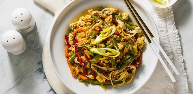 タイのストリートフードのバナー-レストランやカフェで、テーブルの上の皿に豆腐とパッドタイ
