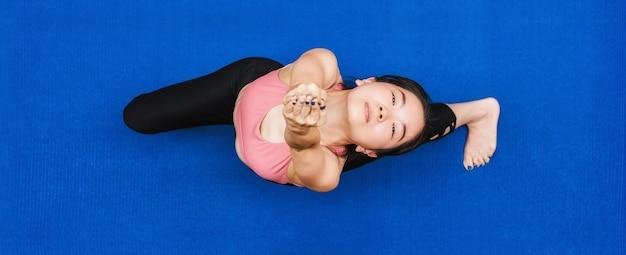トップビューのバナーcovid19が健康に発生したときに自宅からヨガを練習しているアジアの女性