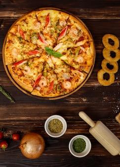 토마토, 튀긴 양파, 오레가노, 롤링 핀, 반죽, 올리브 오일, 가루, 케첩, 피망이 있는 홈메이드 해산물 피자 트레이 배너는 복사 공간이 있는 나무 배경 아래 줄에 있습니다.