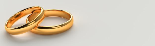 2つの結婚式の金の指輪のバナーは空白のスペースの背景で互いに横たわっています