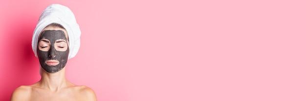 ピンクの背景に黒いフェイスマスクで目を閉じた若い女性のバナー