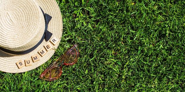 バナー。緑の芝生に麦わら帽子、サングラス、木製の文字。夏という言葉。夏の背景。休暇、週末。
