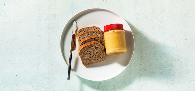 Banner of peanut butter in a jar and whole grain bread with a knife on the table.