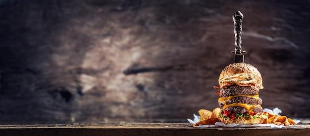 素朴な木製の環境でビーフパティ、溶けたチーズ、卵、コショウを添えたトリプルチーズバーガーに刺されたナイフのバナー写真。