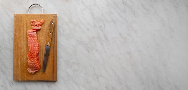 Баннер кусок соленого лосося, нарезанный ломтиками на кухонной доске