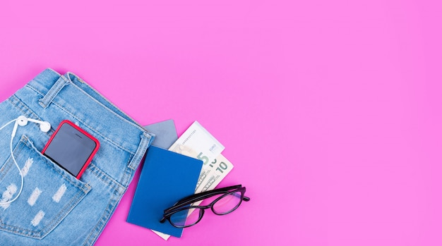 Banner on pink background with blue jeans, money, headphones, 5g internet phone, glasses.