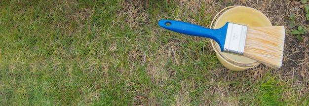 배너, 잔디에 누워 있는 새 나무 판자를 칠하기 위한 준비, 양동이가 있는 페인트 브러시.