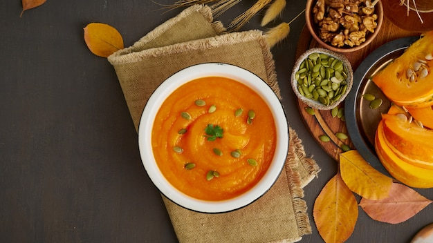 Banner of pumpkin cream soup with walnut and seeds, dark wooden background top view