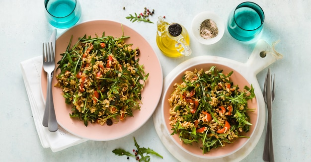 Banner of rice salad with baked bell peppers, arugula, olives and capers.
