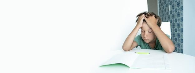Баннер. грустный мальчик с книгой делает домашнее задание в школе. обратно в школу. несчастный школьник с учебниками. дистанционное обучение