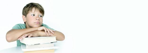 배너. 책을 가진 슬픈 소년은 학교 숙제를 합니다. 학교로 돌아가다. 교과서와 함께 불행 한 남학생입니다. 원격 교육