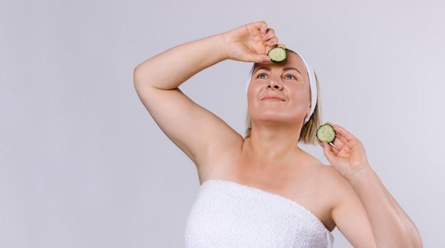배너. 잘 손질 된 피부와 그녀의 머리에 붕대를 가진 고위 여자는 그녀의 손에 오이 조각을 들고 위쪽으로 보입니다. 흰색 바탕에 홈 스킨 케어입니다. 고품질 사진