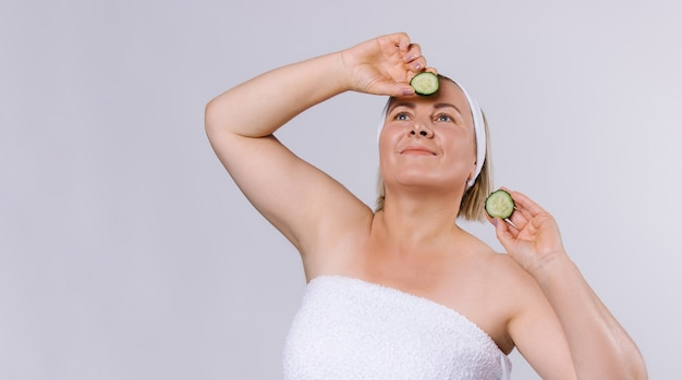 Banner. senior woman with well-groomed skin and a bandage on her head looks upwards holding cucumber slices in her hands. home skin care on a white background. high quality photo