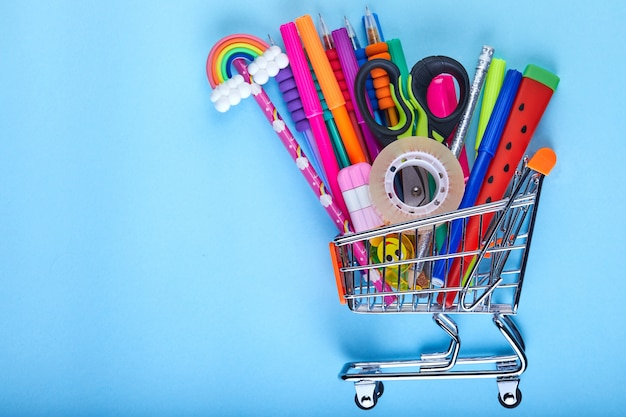Banner of shopping cart with school supply on a blue background with copy space, back to school