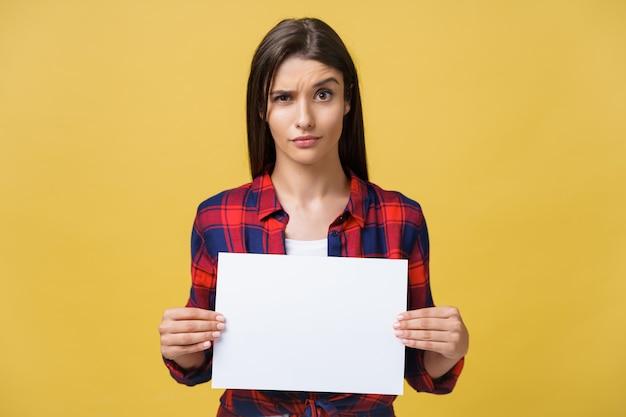 テキストのコピースペースで空白の空の紙の端をのぞくバナーサイン女性。驚いて怖がっている美しい白人女性-面白い。黄色の背景に分離。
