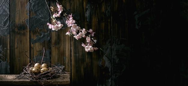 Размер баннера темный деревенский натюрморт пасхи с перепелиными яйцами в гнезде и цветущей вишневой веткой. темная деревянная стена. время пасхальных праздников. копировать пространство