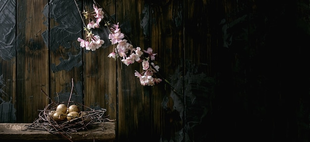 Banner size easter dark rustic still life with quail eggs in nest and blooming cherry branch. dark wooden wall. easter holiday time. copy space