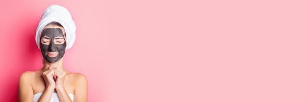 ピンクの背景に黒いフェイスマスクで目を閉じたバナー笑顔の若い女性