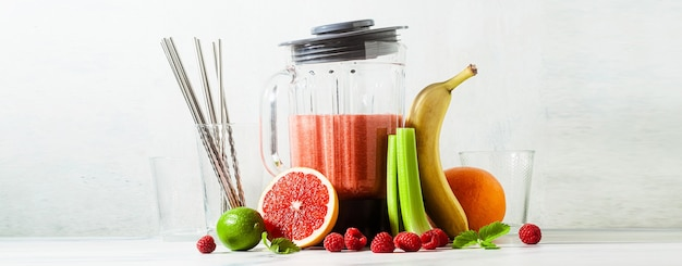 Banner of smoothies in a glass blender bowl and ingredients on the table. not disposable metal tubes. healthly food.