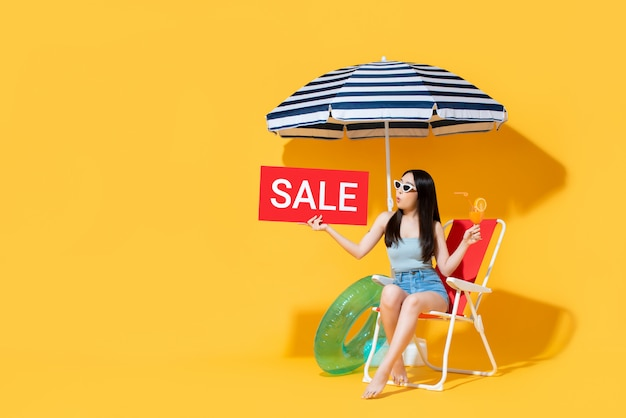 Banner of surprised asian woman in summer outfit showing sale sign