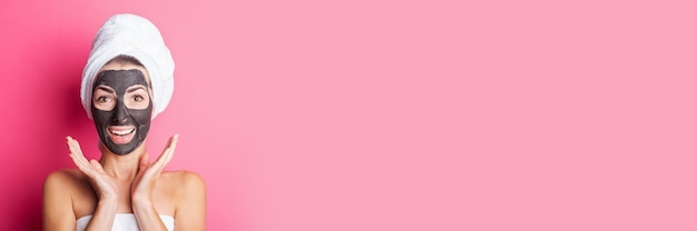 Banner of surprised smiling young woman with black face mask on a pink background