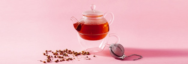 Banner of tea in a glass teapot on a pink background and a metal infuser filter