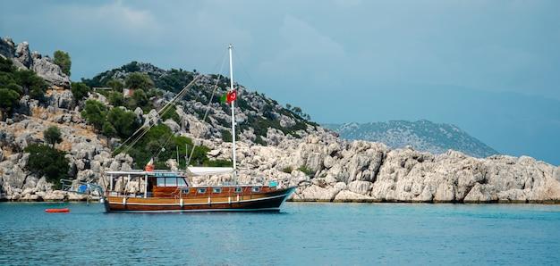 バナー。地中海の美しい夏の山の風景の背景に観光船。