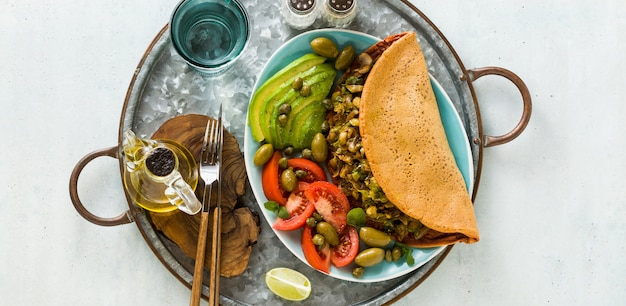 Banner of vegan breakfast of gluten-free egg-free chickpea omelet with fried mushrooms and leek. and a salad of fresh ripe tomatoes, avocados, olives and capers.