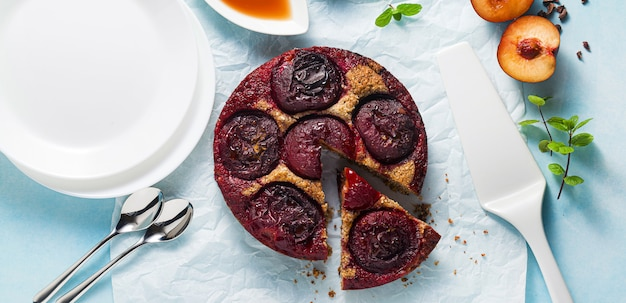 Banner of vegan cake with fresh plums and maple syrup