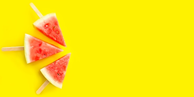 Banner of watermelon slices on sticks like an popsicle on a bright yellow background. copy space.