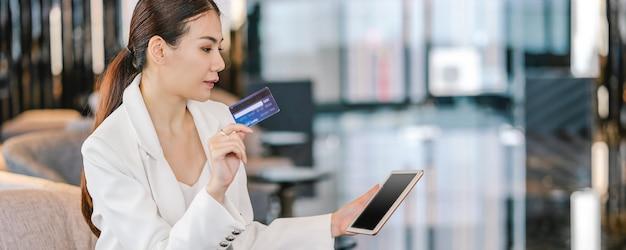 クレジットカードを使用して肖像画のアジアの女性のバナーのwebページまたはカバーテンプレート