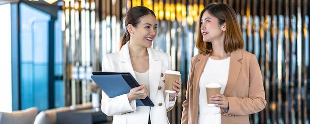 Баннерная веб-страница или шаблон обложки двух азиатских деловых женщин, говорящих во время перерыва на кофе