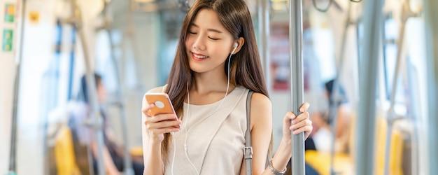 젊은 아시아 여성 승객의 배너, 웹 페이지 또는 표지 템플릿 사용 및 음악 듣기