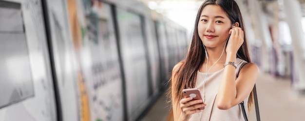 若いアジア女性の乗客を使用して音楽を聴くのバナー、webページまたはカバーテンプレート